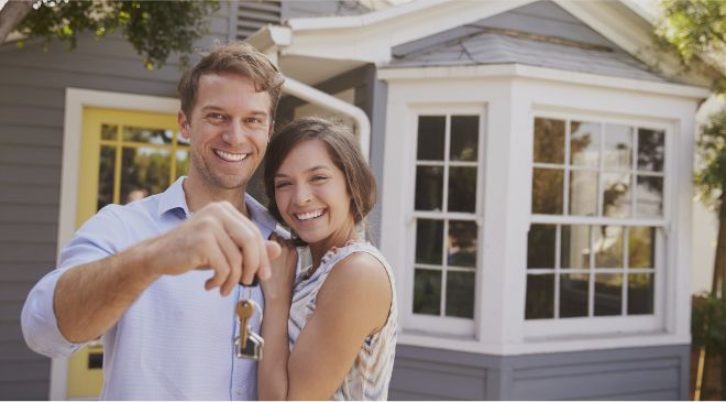 A couple holding a set of keys in front of their house