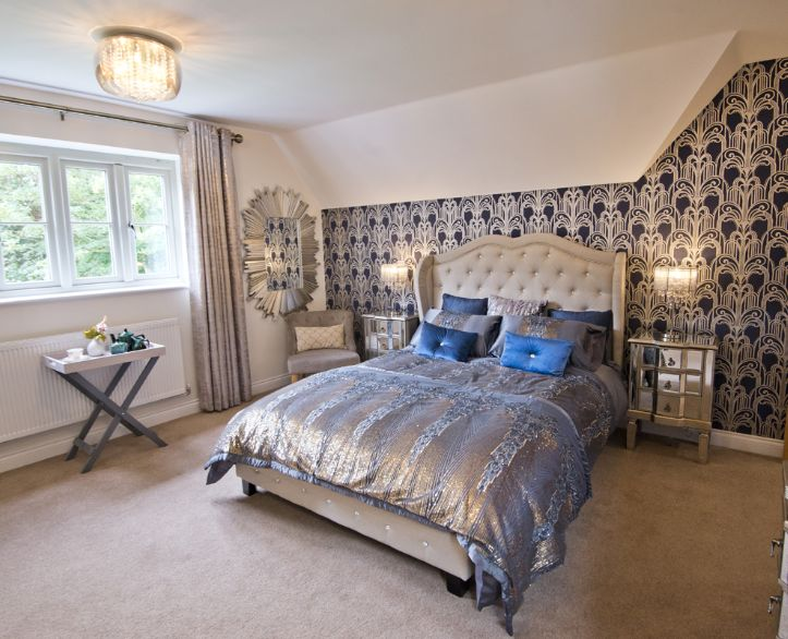 Bedroom with silver bedding and blue pillows